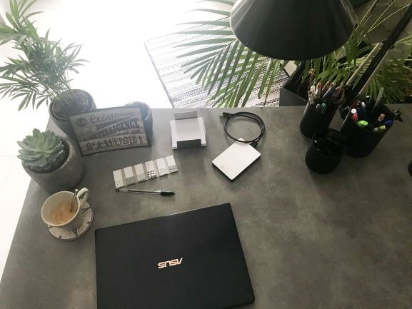 Vue de dessus de mon bureau: quelques petites plantes vertes, une citation inspirante liée à mon activité pro, espace épuré pour plus d'efficacité au quotidien!