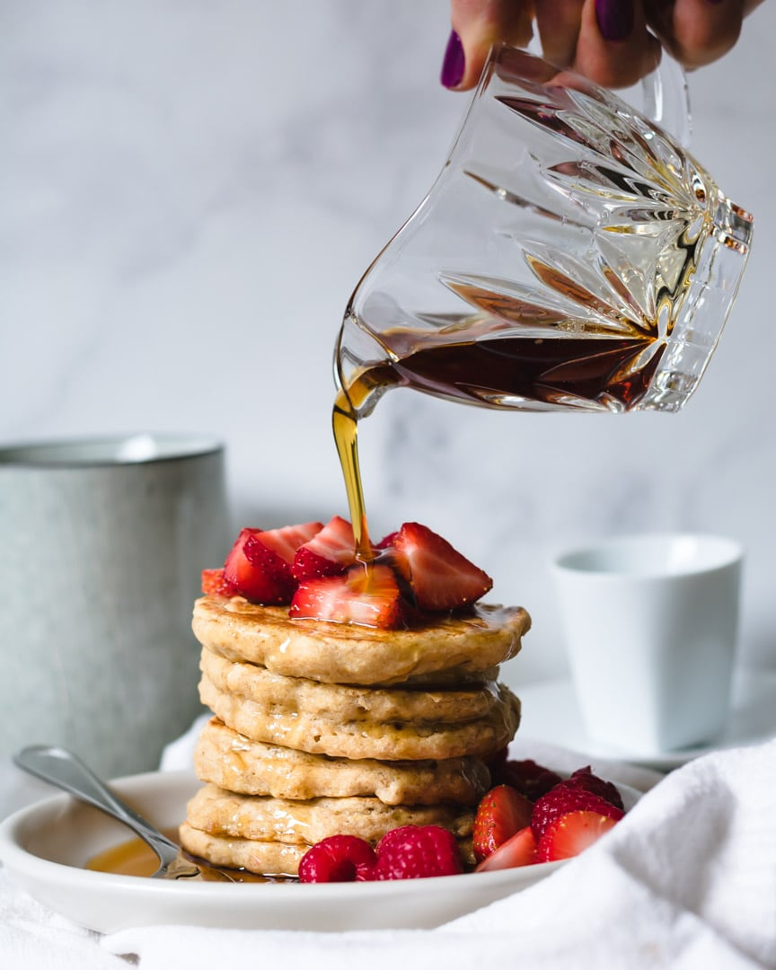 Stack of 7-grain pancakes with strawberries and maple syrup poured on top