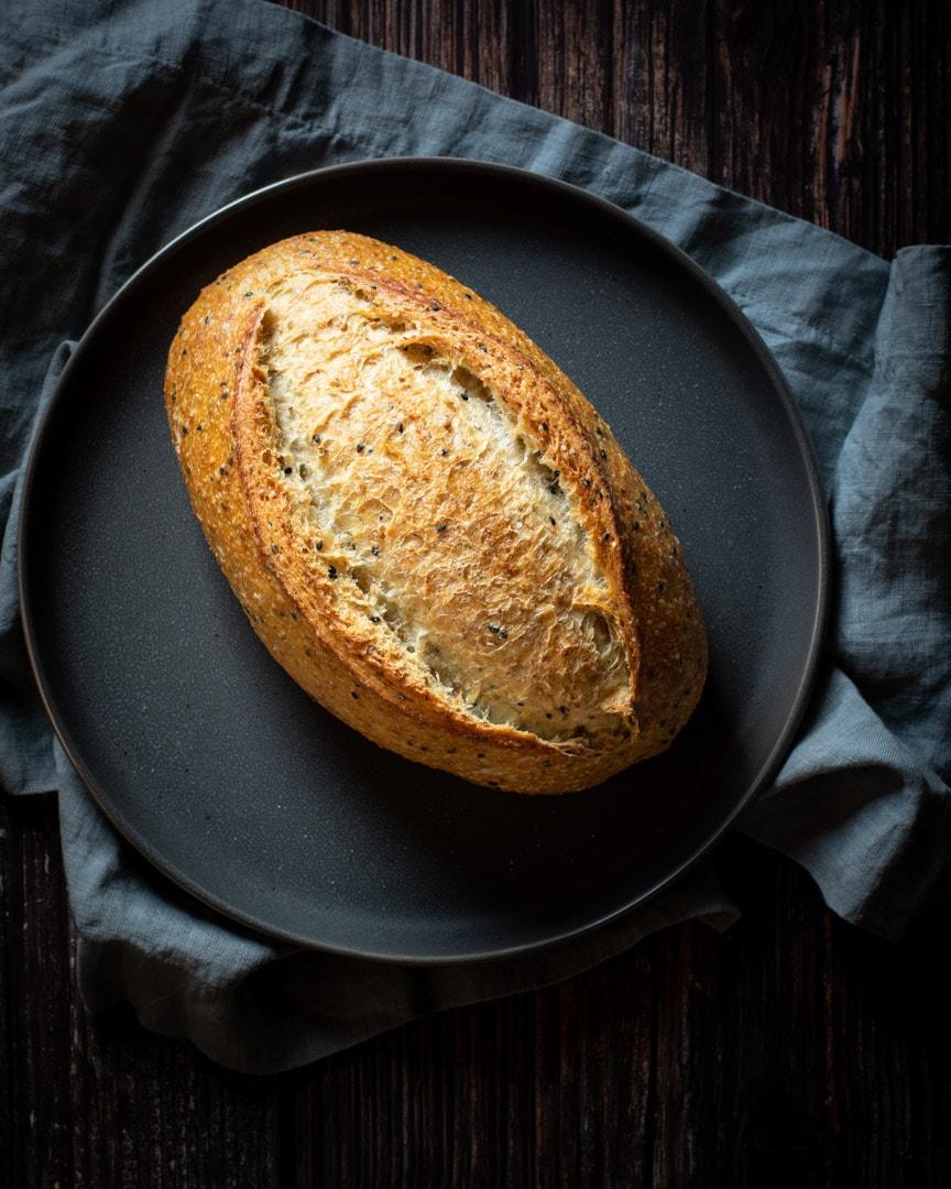 artisan bread loaf on grey plate, grey napkin and dark background