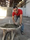 Boucif prépare le béton qui servira à reboucher les trous dans le sol du magasin