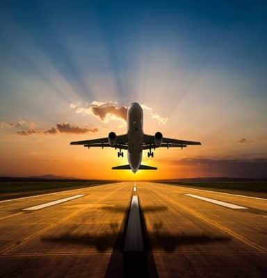 plane taking off at sunset