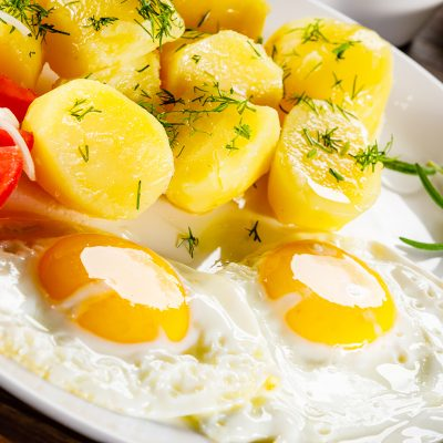 Fried eggs, boiled potatoes and vegetables