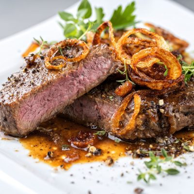 Classic dry aged sliced roast beef with fried onion rings served as closeup on a modern style white plate