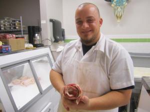 Brad Knaub of Carnivore, holding about a pound of goat bacon, courtesy David Hammond