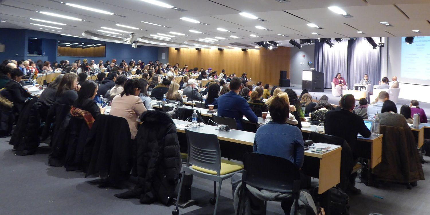 A college classroom with over 100 people seated watching four people speaking on a stage