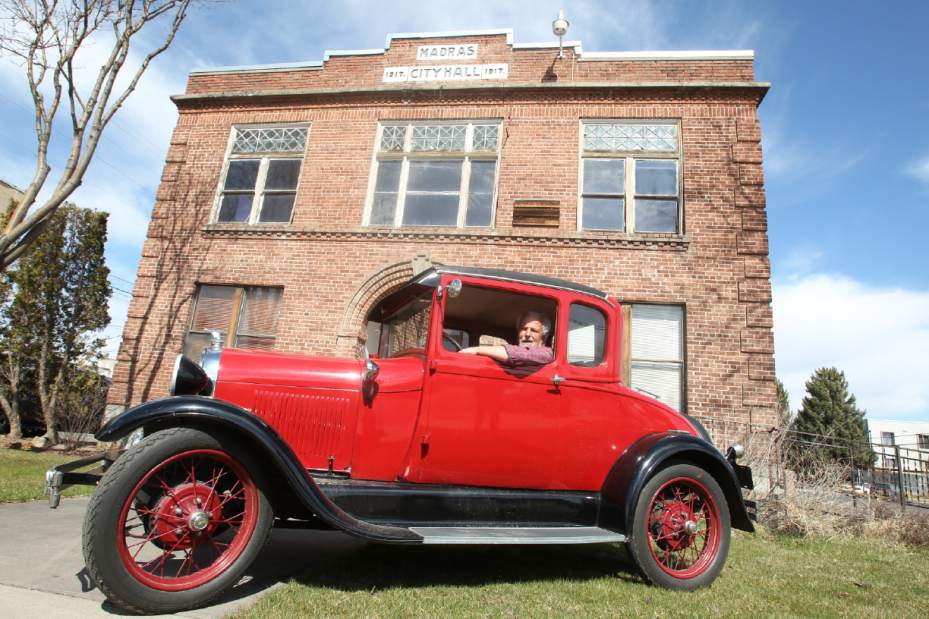 Steve Jansen sits in his Model A Ford in front of the historic Jefferson County Courthouse (Andy Tullis, Bend Bulletin)