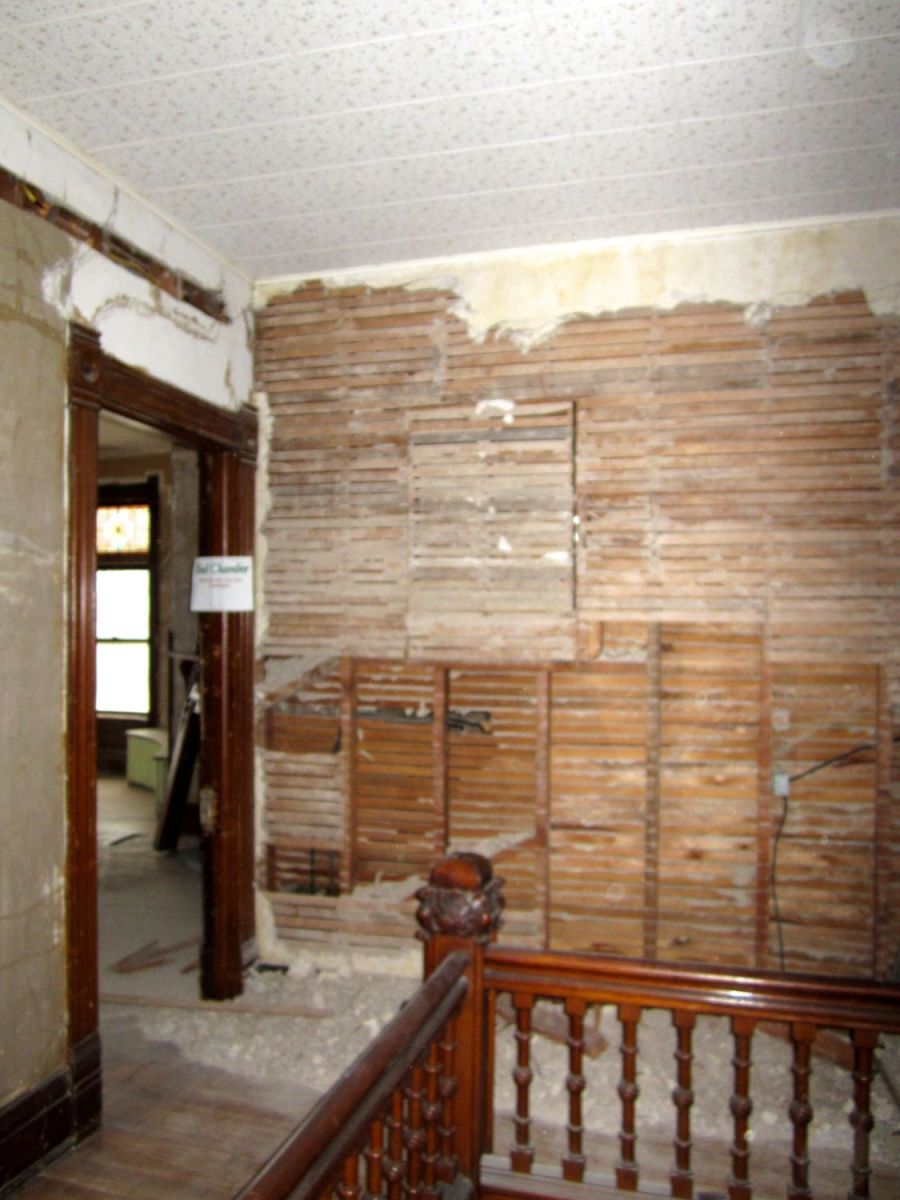 This is the same wall, but to the left (west). If you look close you can see a former window, blocked in with lath strips. Originally, the two bathrooms behind the wall each had a window, so that light from the triple stained glass windows on the north exterior wall could still offer some light into the stair hall. The two windows were later blocked over, thus depriving the stair hall of any natural light.