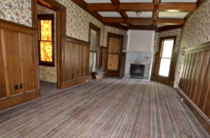 The dining room, and with its circa-1905 wood wainscoting and beamed ceiling. The flooring is carpeting.