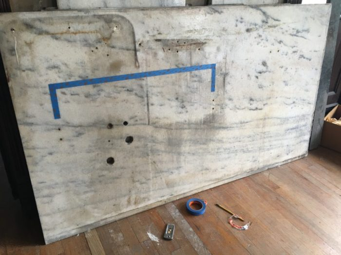 The blue tape indicates the location of an apron vanity. See the pairs of holes under the aprons? These would have been, I assume, mounting brackets. The width is 33-inches, which was a standard vanity width for the period. The height is 30-inches, also standard (36-inches is now standard). To the far right is another pair of holes. I feel confident that these were for a clamp holding the pipe to a high-tank toilet.