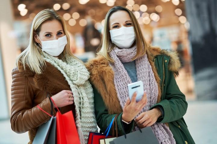 Zwei blonde, weiße Frauen mit MNS-Masken lachen warm gekleidet mit Einkaufstaschen und Handy  in der Hand in die Kamera.