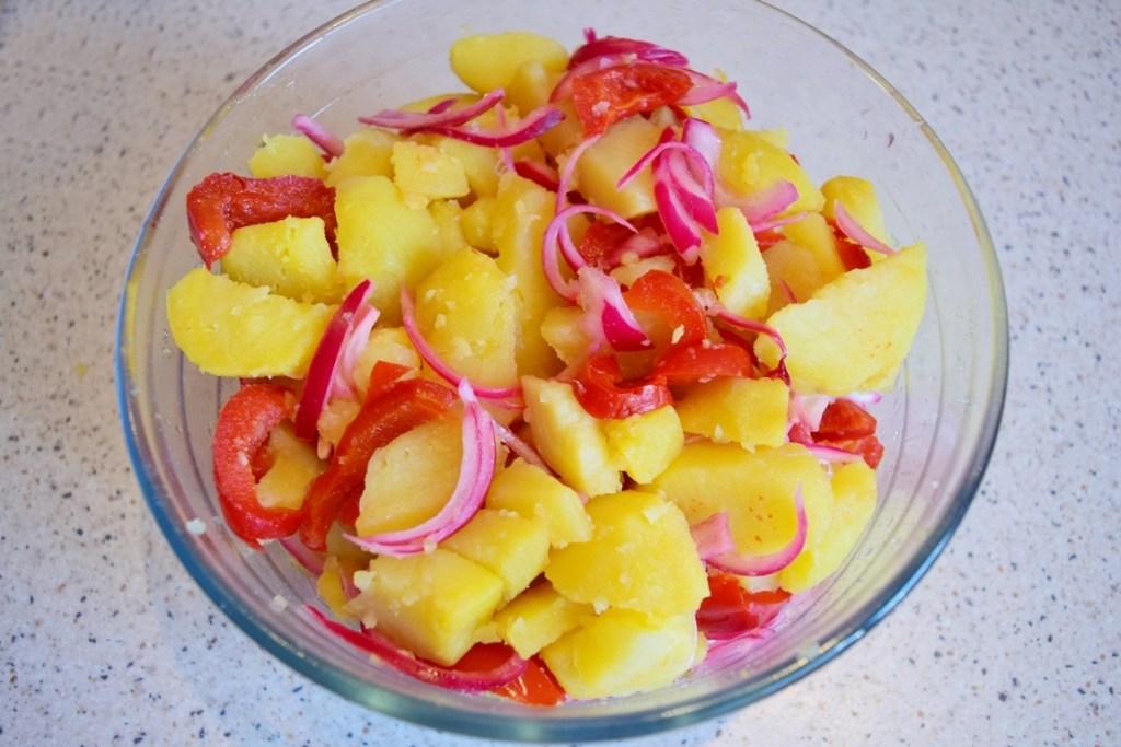 Bol de sticlă cu cartofi, ceapă roșie și gogoșari murați