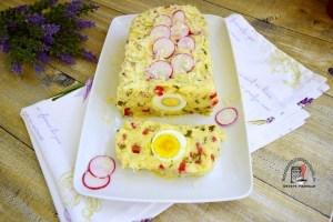 Aperitiv din cartofi cu ouă fierte, feliat pe un platou alb