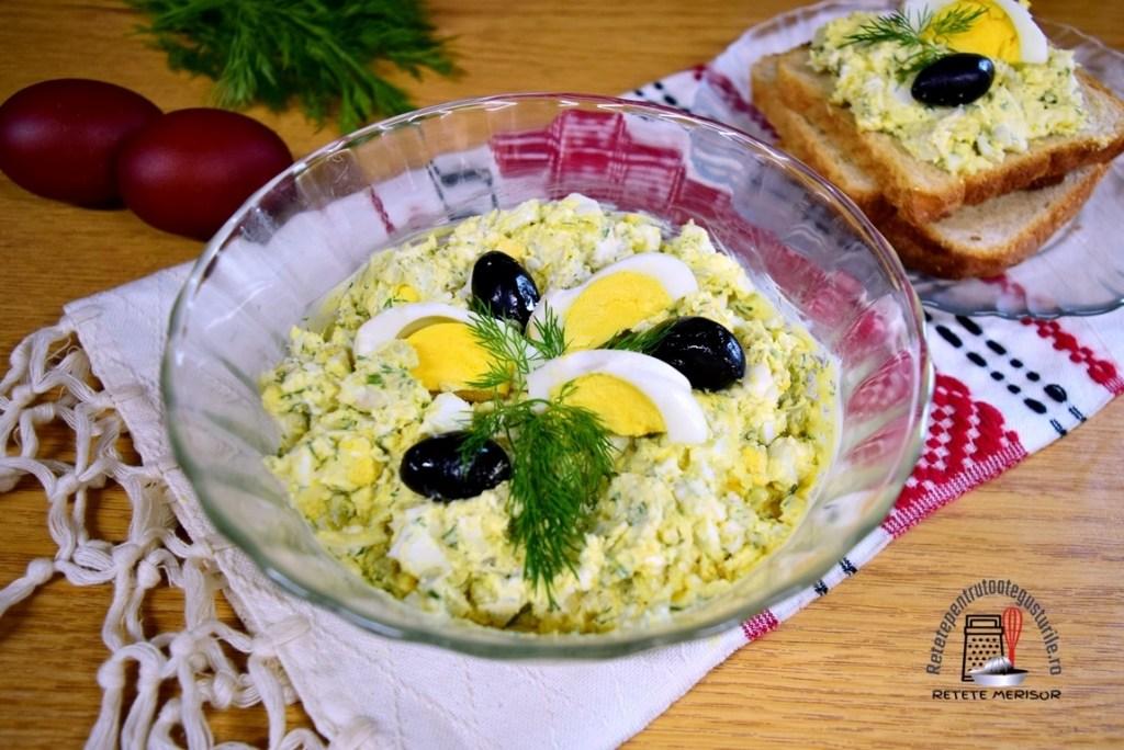 Pastă de ouă cu brânză și mărar, decorată cu măsline, într-un bol de sticlă
