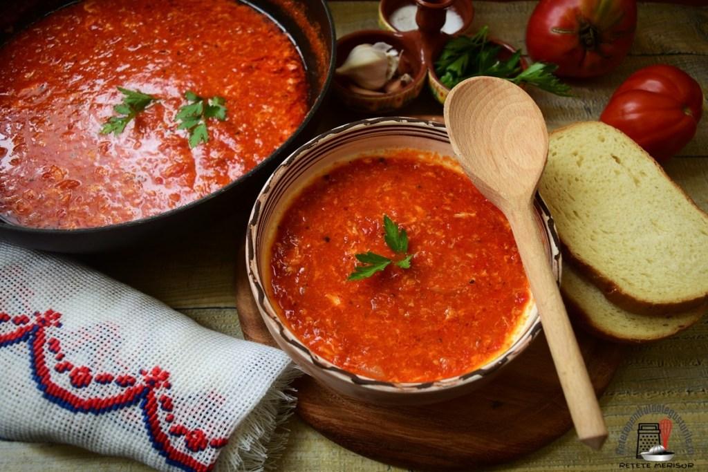 Porție de mâncare de roșii cu usturoi și ouă, într-un bol de servire, alături de tigaia cu mâncarea de roșii