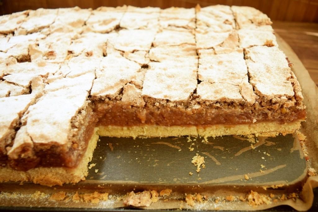 Prăjitură cu mere și bezea cu nucă, porționată în tavă