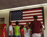 Master Sgt. Kelly K. Collett, broadcast manager, third from left, and his family take a tour of the TEC TV studios June 6, 2016, at the I.G. Brown Training and Education Center in Louisville, Tenn., to include the American flag display in Spruance Hall. The flag was last flown on campus July 29, 1986, after a 16-year journey over the capitols of every state and territory in the United States. (U.S. Air National Guard photo by Master Sgt. Mike R. Smith/released)