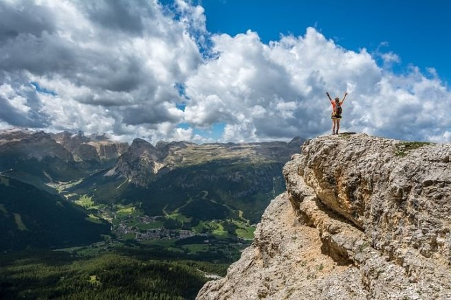 Hiker achieves her goal by climbing to the top of a mountain.