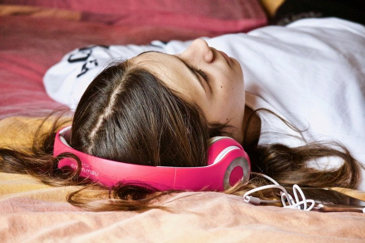 girl wearing headphones, lying down on bed