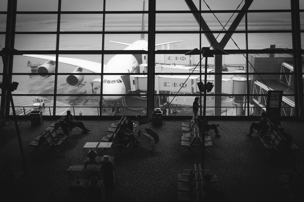 Black and white picture of an airport gate, camera looking out the window  viewing an airplane being boarded.