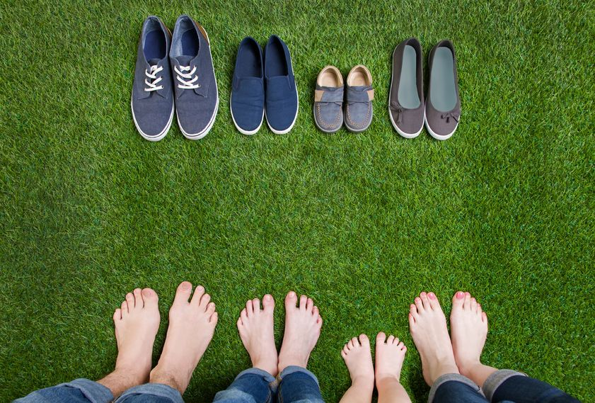 39571410 - family legs in jeans and shoes standing  on grass
