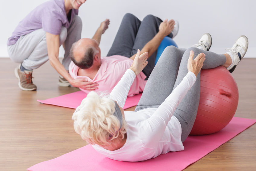 54417213 - senior exercising on gym ball with professional instructor.