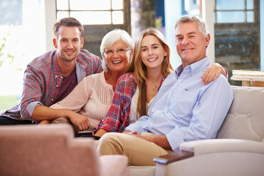 41461615 - family with adult children relaxing on sofa at home together