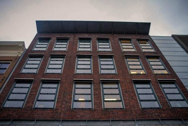 A foto mostra uma construção feita em tijolos, com janelas de vidro descobertas, típica construção de Amsterdam.