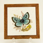 Beautiful blue butterfly and cottage seen on an American made ceramic tile. Framed in teak wood.