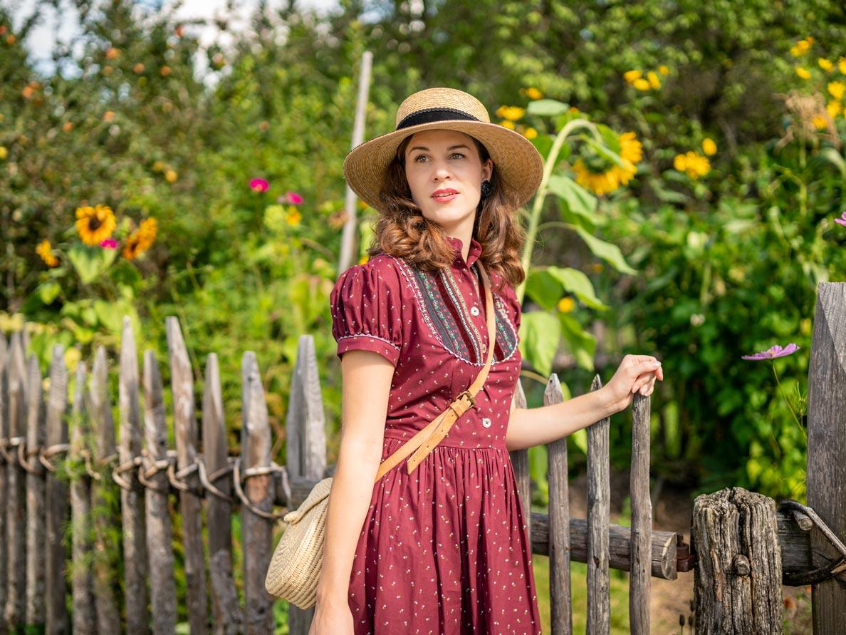 RetroCat mit einem Trachtenkleid von Lena Hoschek vor einem Garten