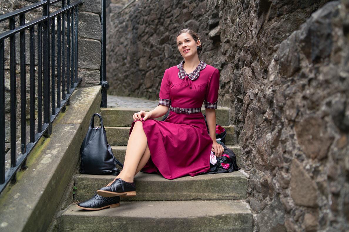 RetroCat mit Schnürern und lila Retro-Kleid auf einer Burg