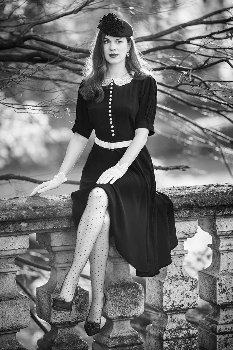 RetroCat mit schwarzem 40er-Jahre-Kleid und Nylons mit Punkten
