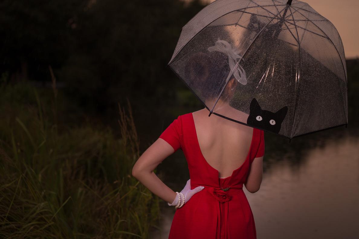 RetroCat trägt ein Kleid mit tiefem Rückenausschnitt und einen stylishen Regenschirm
