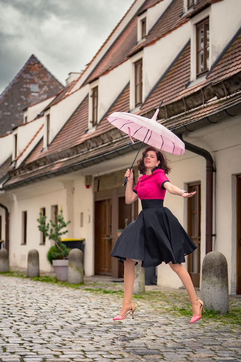 RetroCat mit einem pinken Retro-Kleid und einem rosa Pagoden-Regenschirm