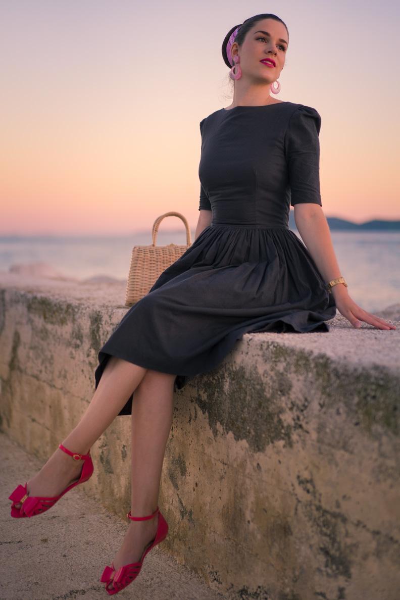 RetroCat trägt ein graues Retro-Kleid und pinke Jelly-Sandalen