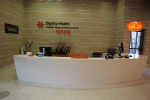 "A branded ""Hello"" desk immediately greets patients and visitors upon entering the lobby from the exterior."