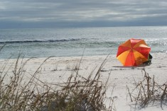 the pop of color of the beach umbrella against the waves and the rain clouds