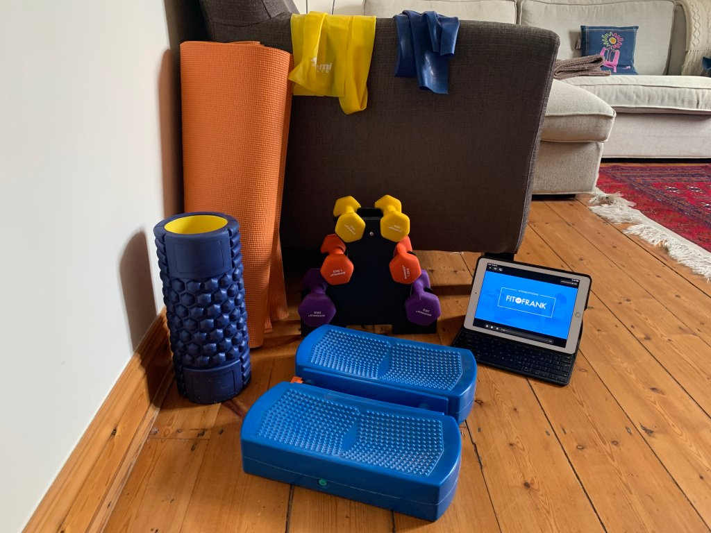 Picture of exercise equipment including a yoga mat, resistance bands, weights, a stepper, foam roller and Fit with Frank online bootcamp videos. Exercise and physiotherapy can help you move on from the depression about your illness or injury.