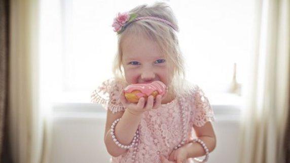 Une petite fille qui goûte unepâtisserie