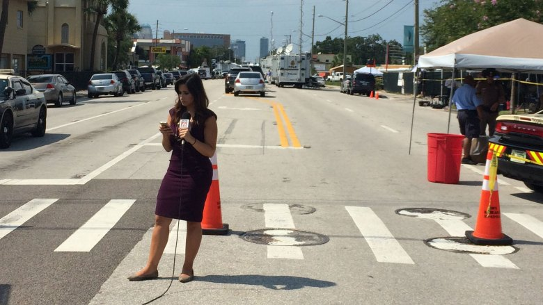 A newscaster stands in the middle of South Orange Avenue, the Pulse nightclub in the distance behind her.