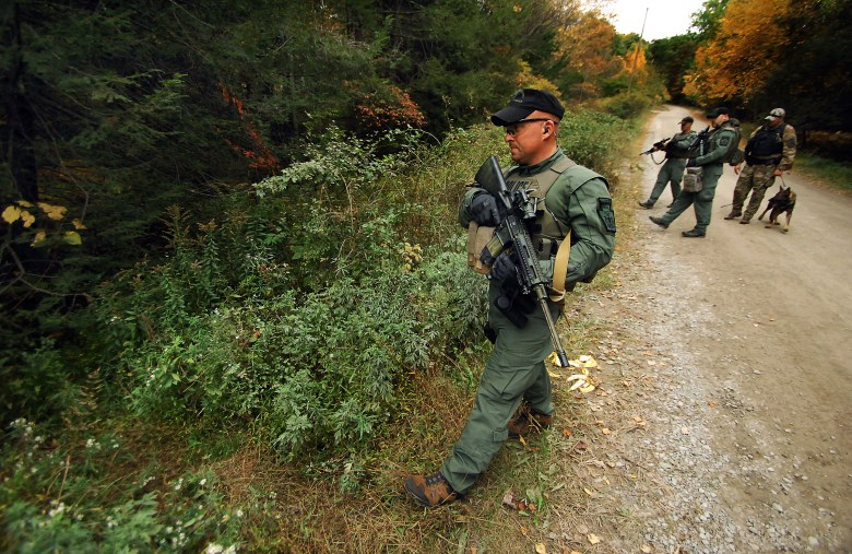 A member of the Scranton Police Special Operations Group enters the woods in October 2014 near Canadensis, Pa., in a search for Eric Matthew Frein, an anti-government radical later convicted of killing a state trooper. Frein was caught after a 48-day manhunt.