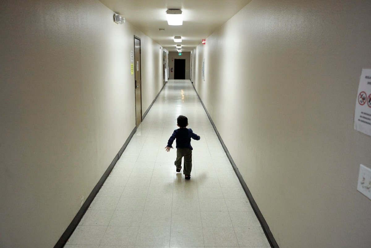 A small boy runs down a long empty hallway on his own.