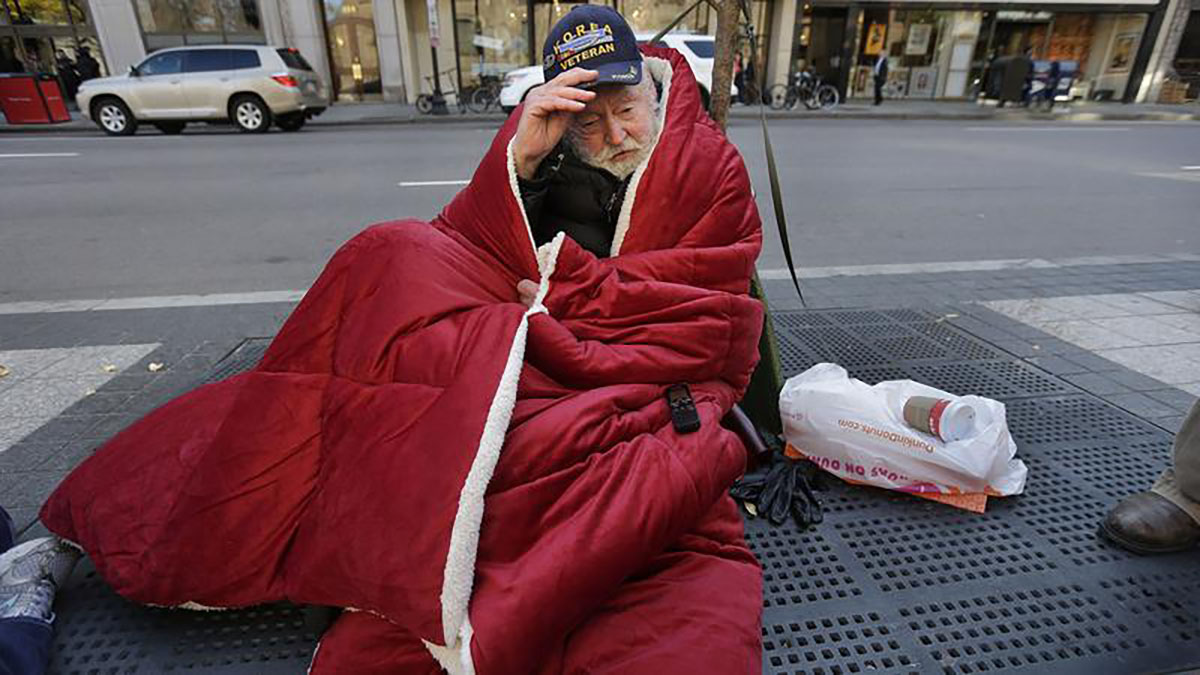 An older white man with a beard and a Korean War Veteran hat sits on the sidewalk wrapped in a sleeping bag