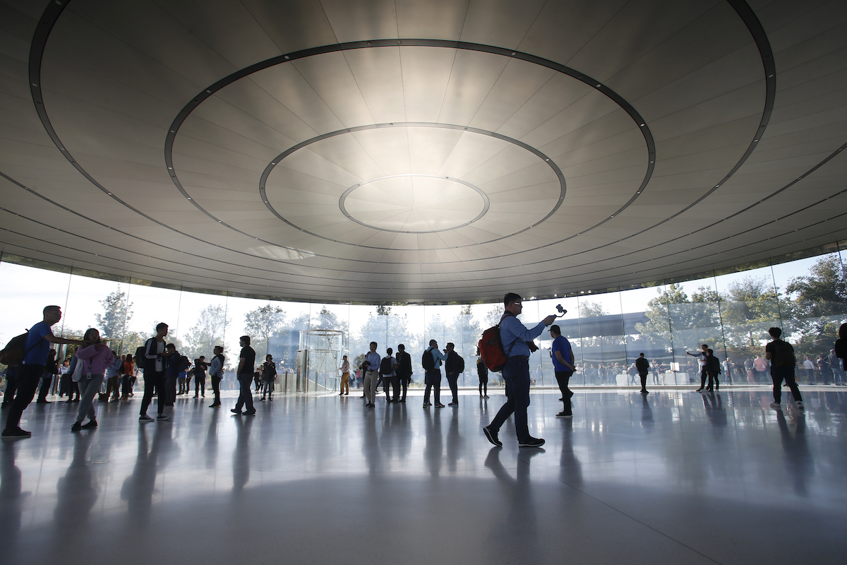 The interior of the Steve Jobs Theater looks futuristic, as people wander around the space talking and taking photos.