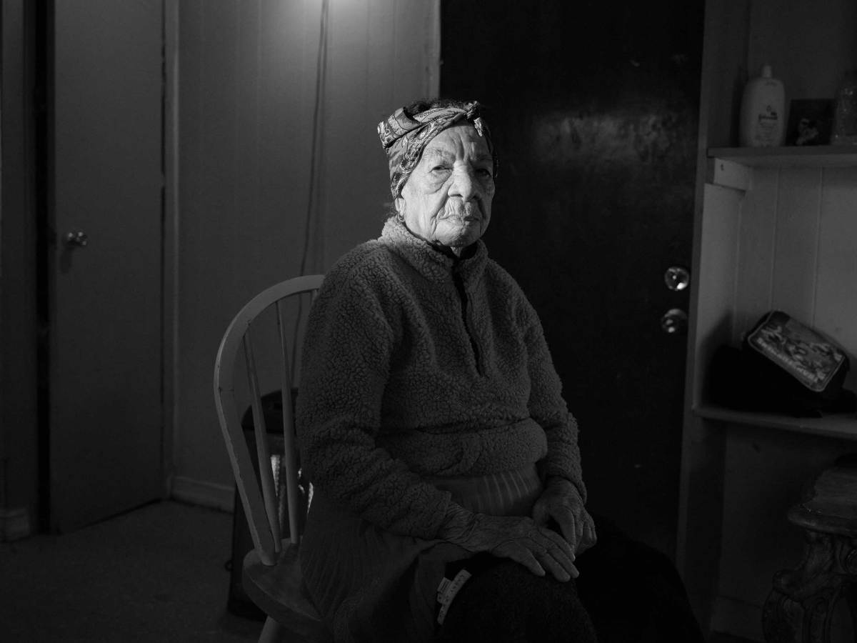 A black and white portrait of Doña Amalia - a ray of sunlight illuminates her face as she sits in a chair in her house.