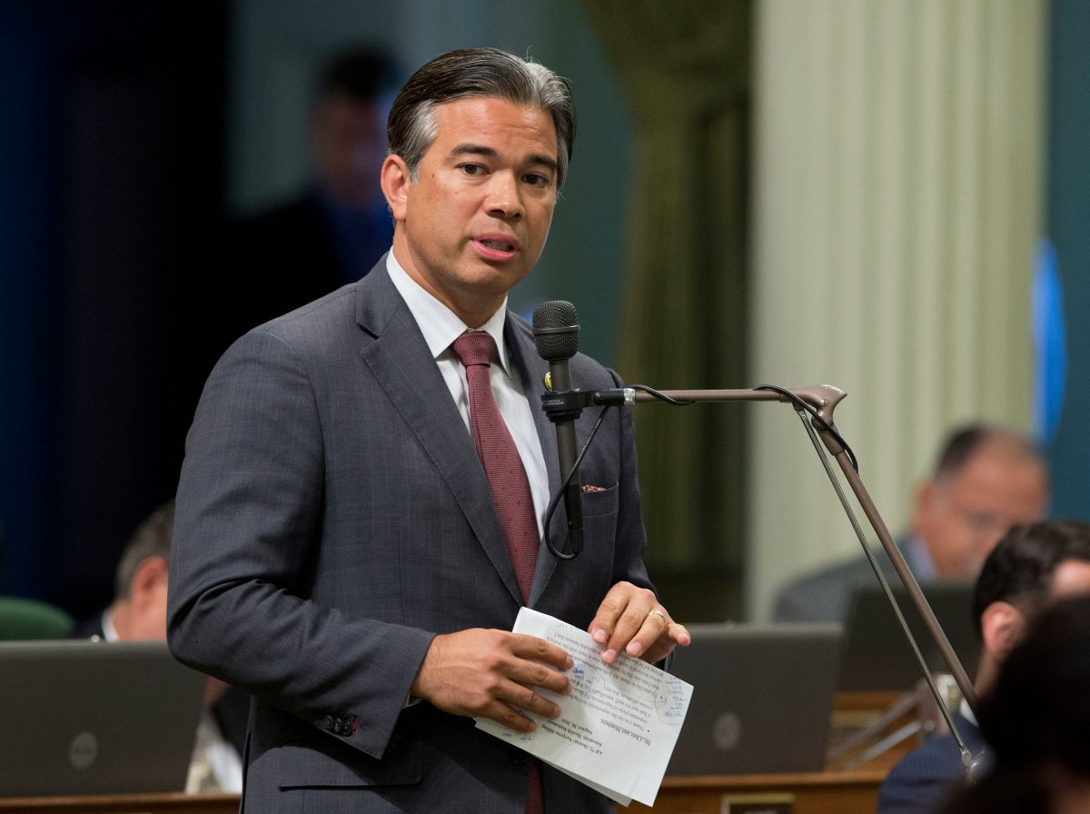 Rob Bonta, wearing a gray suit, stands at a microphone holding a piece of paper.