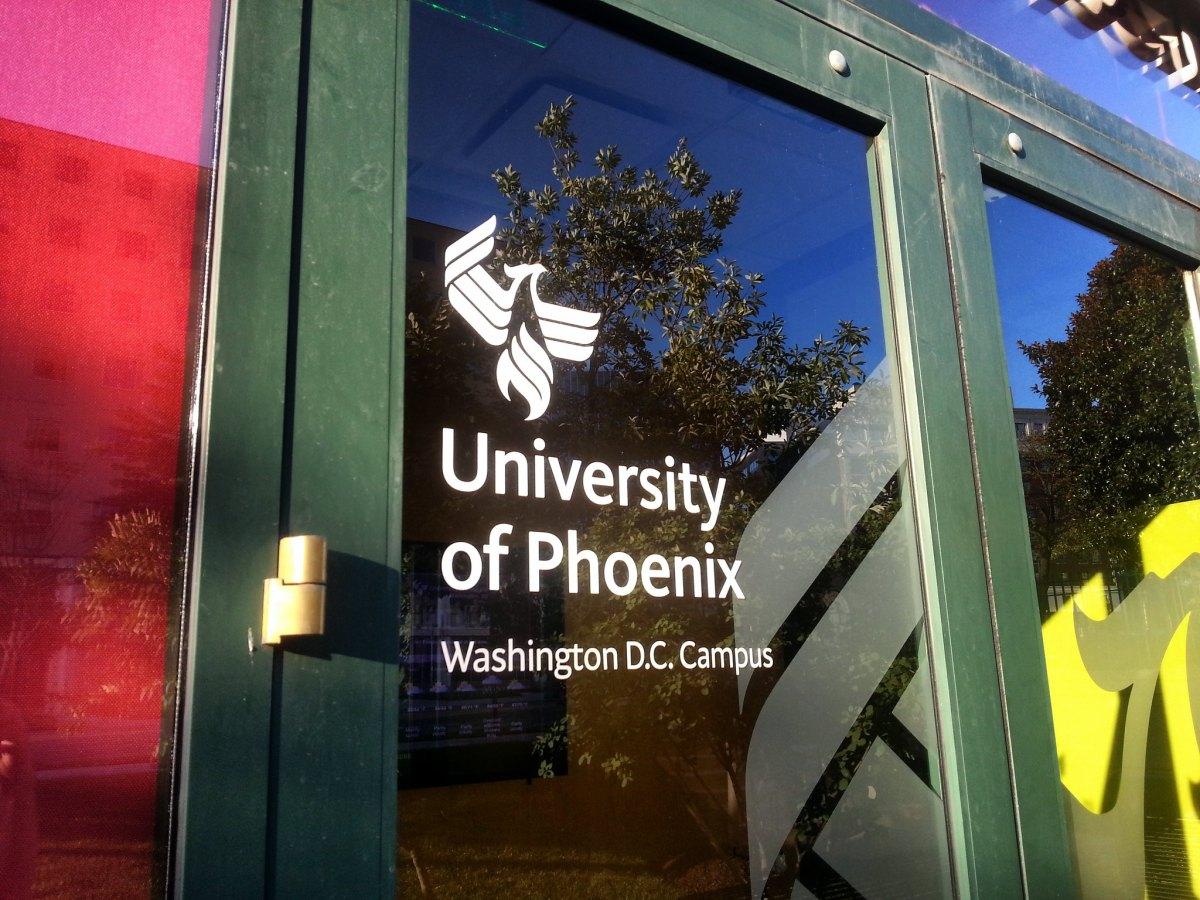 The glass front door of a building bears the logo of University of Phoenix