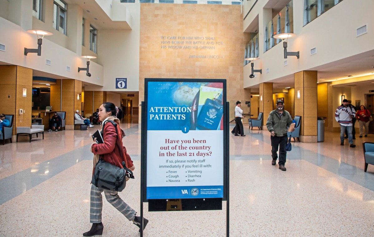 """A woman walks past a sign in a veterans affairs hospital that says """"attention patients"""" and warns of Coronavirus."""
