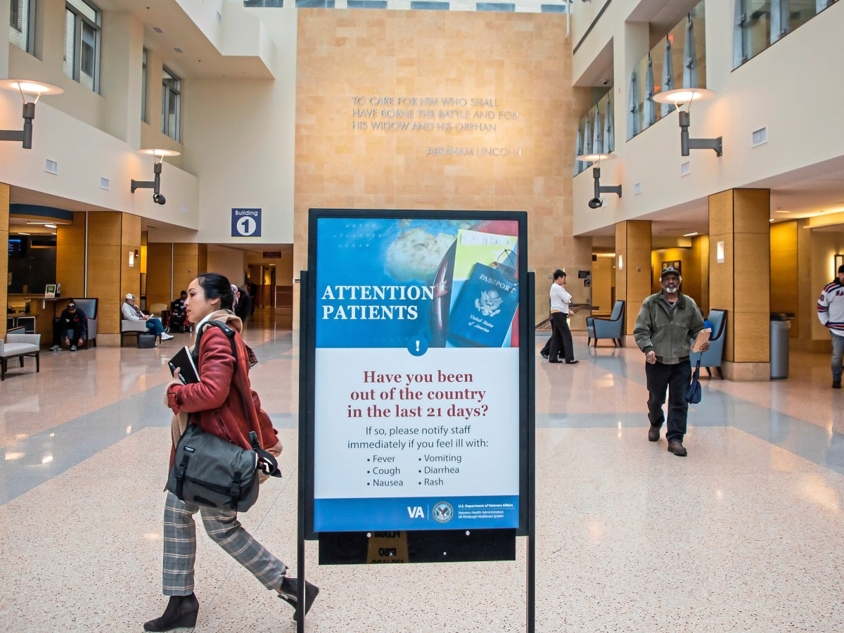 "A woman walks past a sign in a veterans affairs hospital that says ""attention patients"" and warns of Coronavirus."