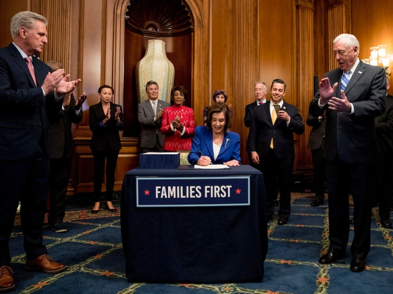 """Nancy Pelosi, wearing a blue suit, sits at a table signing a bill. A sign reading """"families first"""" is on the table. A group of officials surrounding her applauds."""