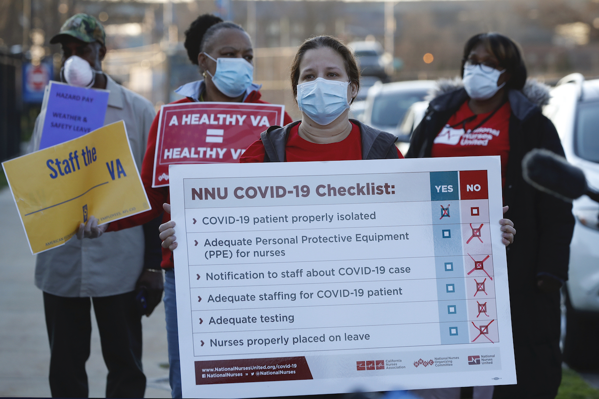 Workers wearing red shirts and surgical face masks hold protest signs outside the VA.